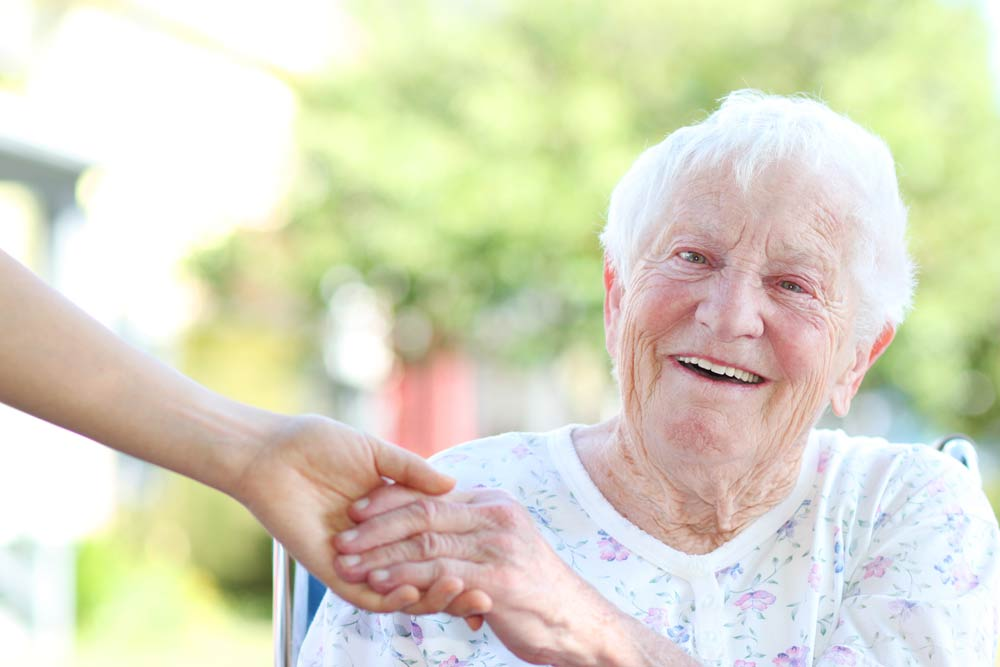 Senior Woman Holding Hand of Caregiver